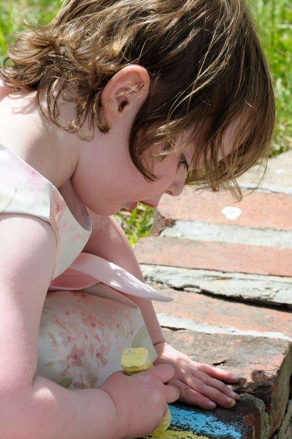 Portrait d'une petite fille mignonne en dehors de l'écriture sur des briques avec la craie de trottoir photo libre de droits