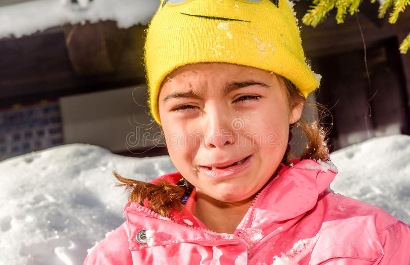 Portrait d'une petite fille pleurant parce qu'elle est froide dans la neige photo libre de droits