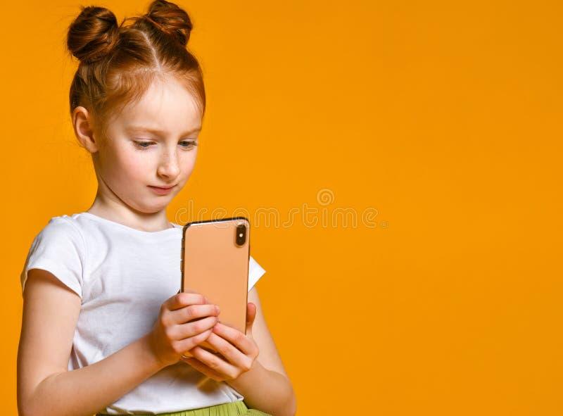 Portrait d'une petite fille rousse semblant le t?l?phone intelligent, se tenant contre un mur jaune photographie stock libre de droits