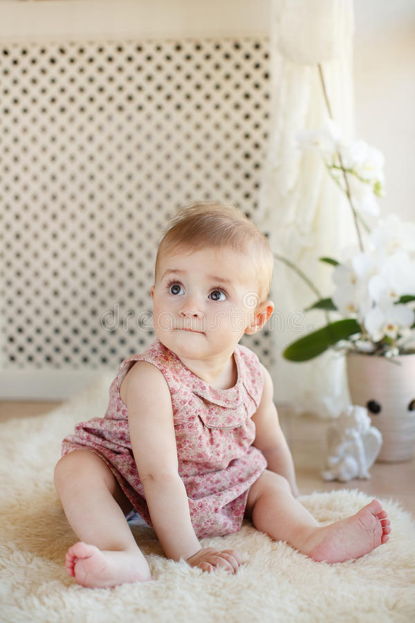 Portrait d'une petite fille s'asseyant sur le plancher photos stock