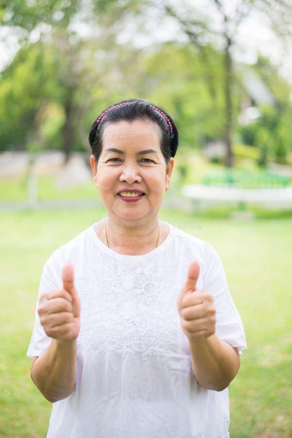 Portrait d'une position asiatique pluse ?g? et de montrer le pouce ? ext?rieur, ? heureux et du sourire de femme, temps de libert photo stock