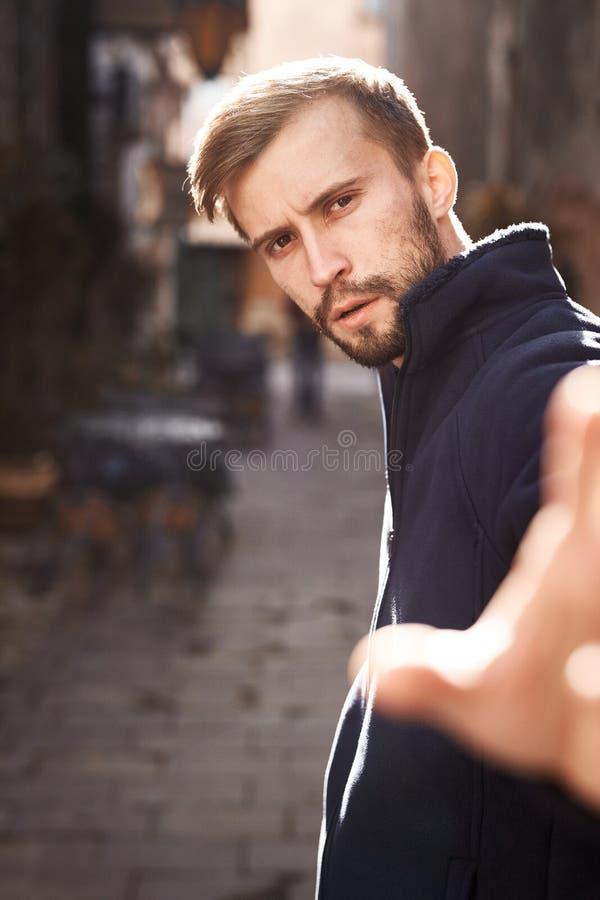 Portrait d'une position de jeune homme dans le contre-jour sur la rue dans la vieille ville photos stock