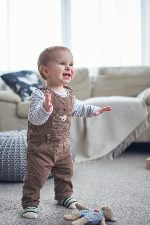 Portrait d'une position de 1 an mignonne de bébé garçon sur le plancher le concept de premières étapes photo libre de droits