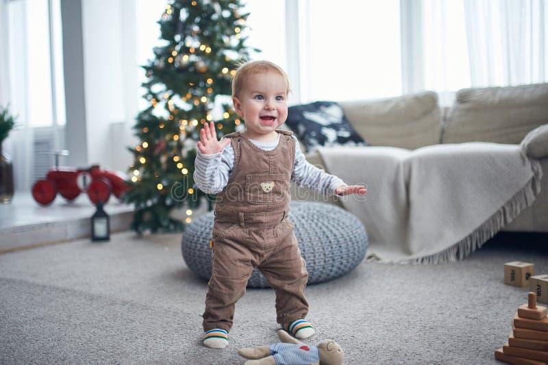 Portrait d'une position de 1 an mignonne de bébé garçon sur le plancher le concept de premières étapes décorations de Noël sur un photographie stock
