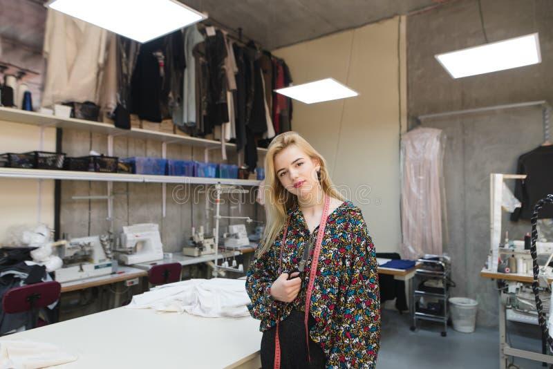 Portrait d'une position de sourire d'ouvrière couturière dans le studio avec des ciseaux dans des ses mains et la pose sur la cam photographie stock