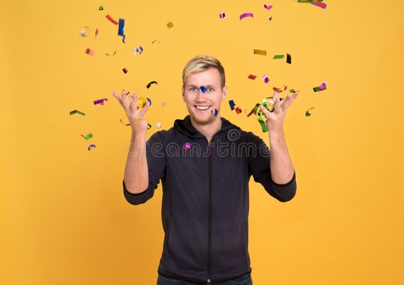 Portrait d'une position gaie d'homme debout sous la pluie de confettis photo libre de droits