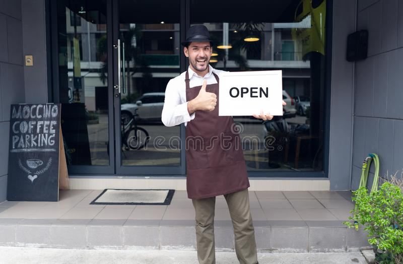 Portrait d'une position heureuse de serveuse à l'entrée de café et de tenir le signe ouvert dans le café avant Petite entreprise  image stock