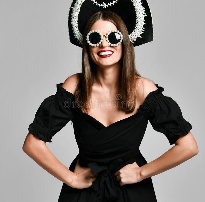 Portrait d'une robe élégante de noir de brune, des lunettes de soleil noires, d'un chapeau de kokoshnik, de longs cheveux et d'un image stock