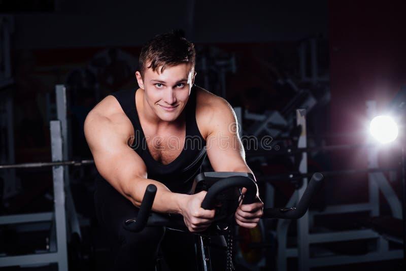 Portrait d'une séance d'entraînement belle d'homme sur la forme physique l'obscurité de vélo d'exercice au gymnase photos stock