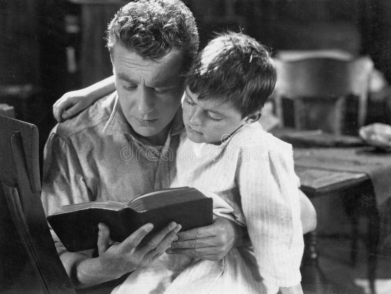 Portrait of dad reading bedtime story to son stock image