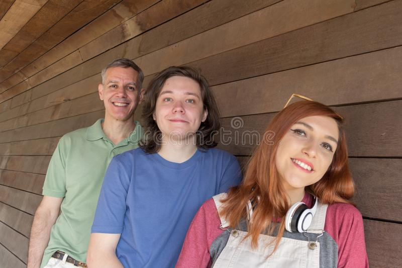 Portrait of Dad and teenage son and daughter against wooden wall stock photo