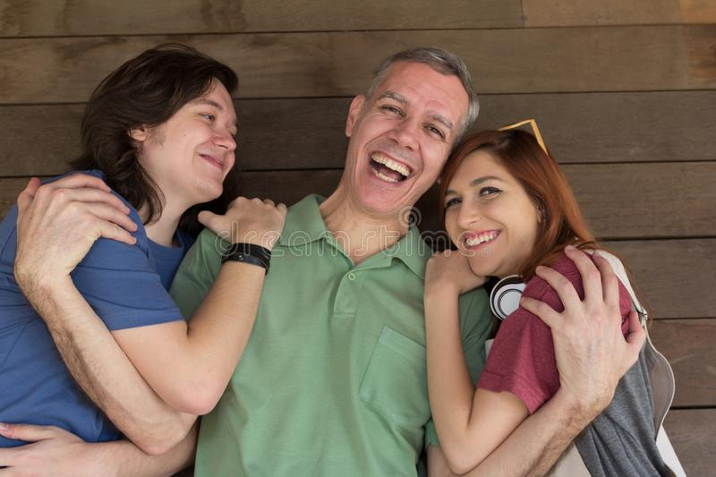 Portrait of dad and teenage son and daughter holding each other. royalty free stock photography