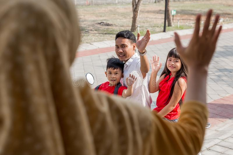 Daddy taking his kids to school by motor bike. Portrait of daddy taking his kids to school by motor bike waving goodbye to mommy royalty free stock image