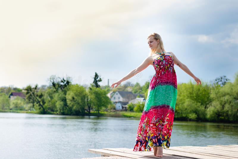 Portrait of dancing beautiful blonde young lady in long light dress at water lake on summer green outdoors stock photo