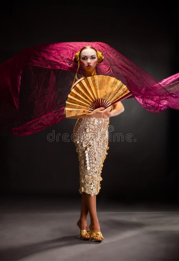 Portrait of a dancing young woman with flying fabric stock image