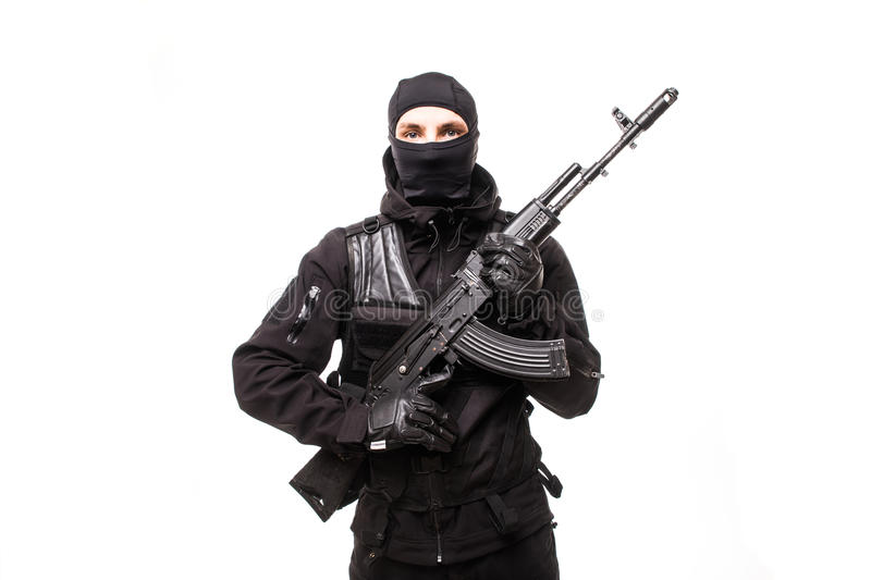 Portrait of dangerous bandit in black wearing balaclava and holding gun in hand royalty free stock photo