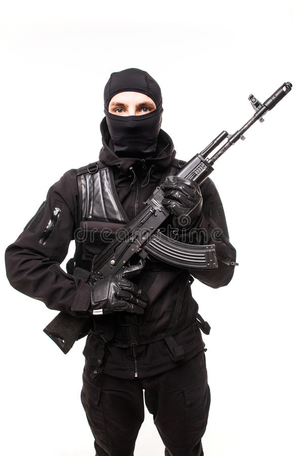 Portrait of dangerous bandit in black wearing balaclava and holding gun in hand stock photography