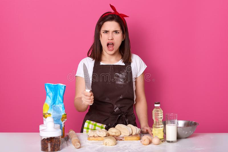 Portrait of dangerous emotional housewife standing isolated over pink background in studio, having impressed facial expression,. Holding knife in hand, opening stock image