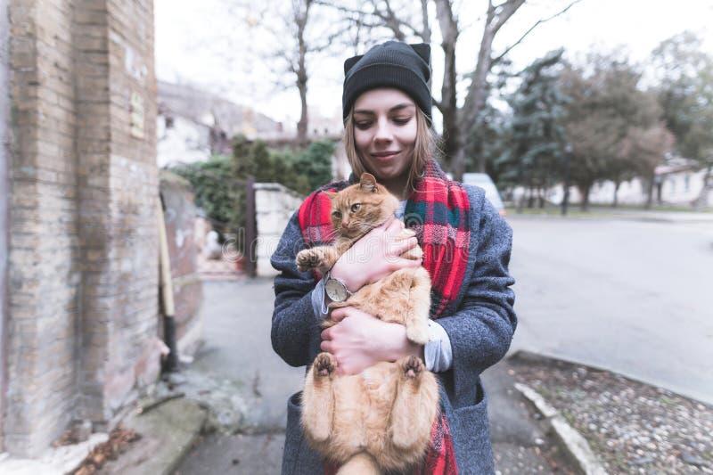 Portrait dans la fille heureuse de tons froids dans un manteau de chapeau et une écharpe rouge tenant un chat rouge Concept d'amo image stock