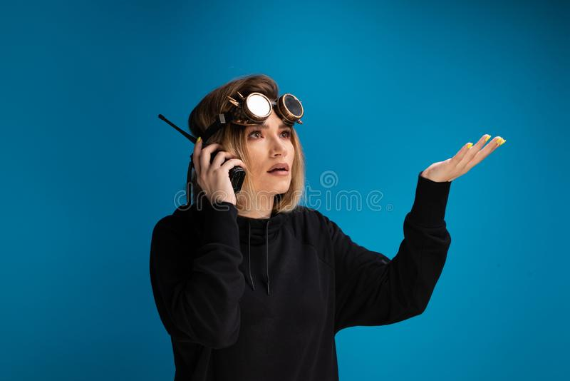 Portrait of dark blonde girl with steam punk glasses using a walkie talkie communication device arguing and looking royalty free stock image