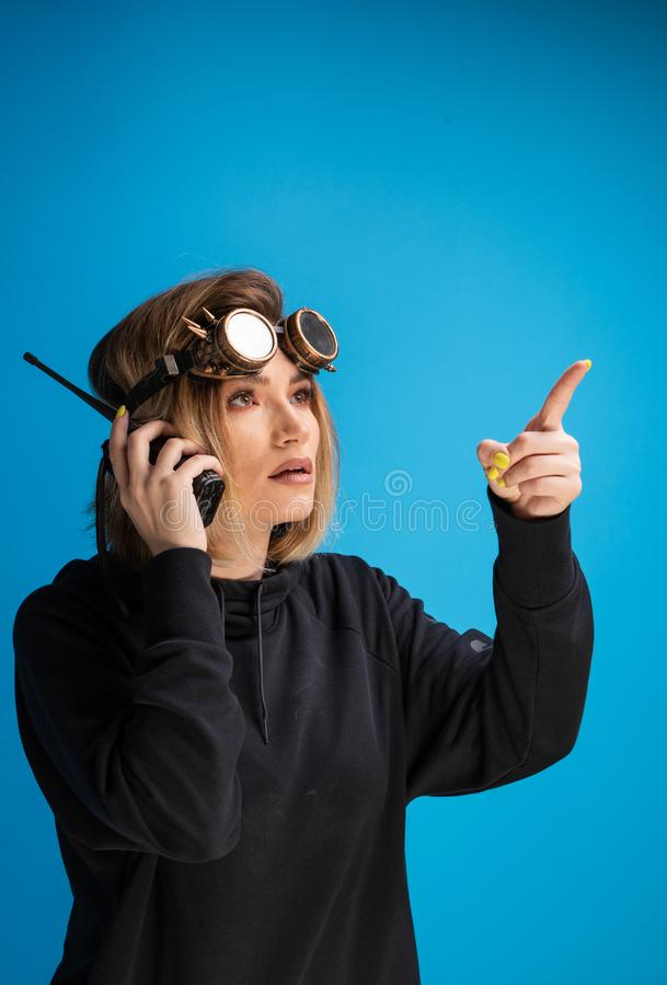 Portrait of dark blonde girl with steam punk glasses using a walkie talkie communication device and pointing with finger royalty free stock image