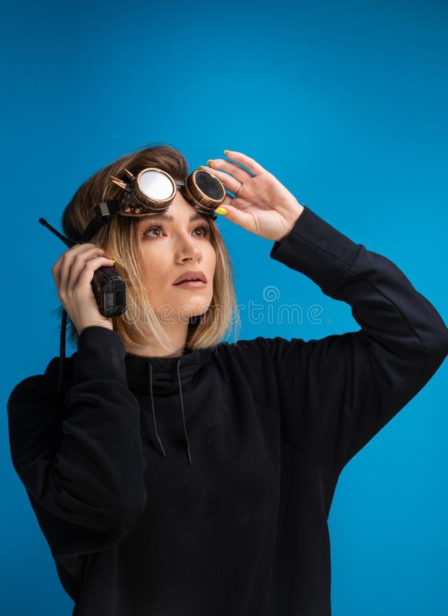 Portrait of dark blonde girl with steam punk glasses using a walkie talkie communication device stock photos