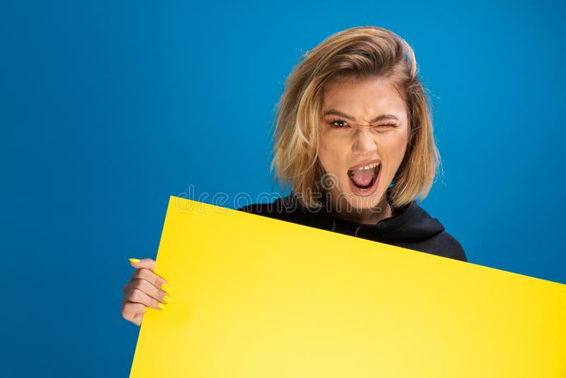Portrait of dark blonde woman winking cheerful while holding cardboard paper stock photo