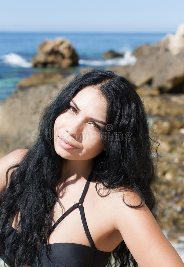 Portrait of dark haired young woman at sea royalty free stock photography