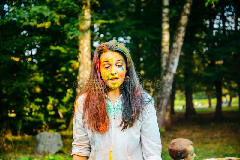 Portrait of dark long hair woman all in holi paints stock images