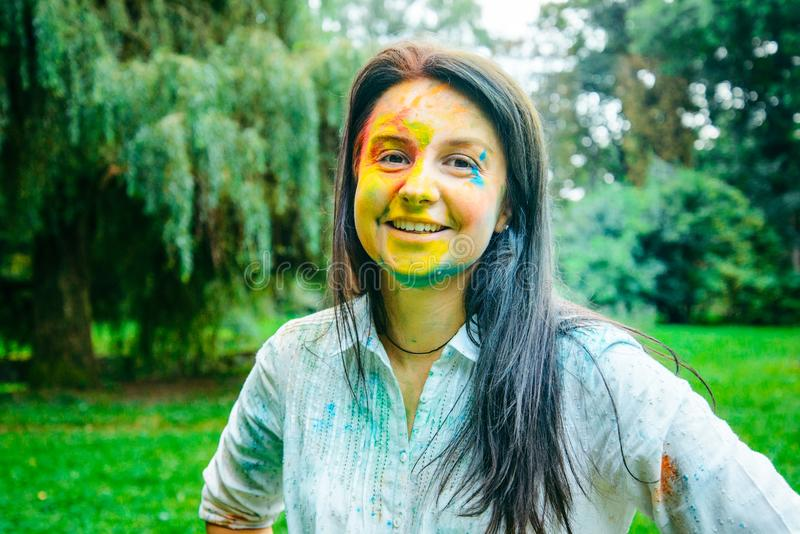 Portrait of dark long hair woman all in holi paints. In city park royalty free stock photography