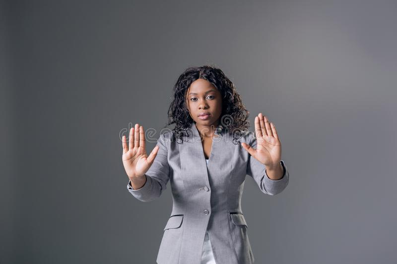 Portrait dark-skinned beautiful woman a gray jacket with dark curly hair, looking into the camera with a serious looks royalty free stock photo