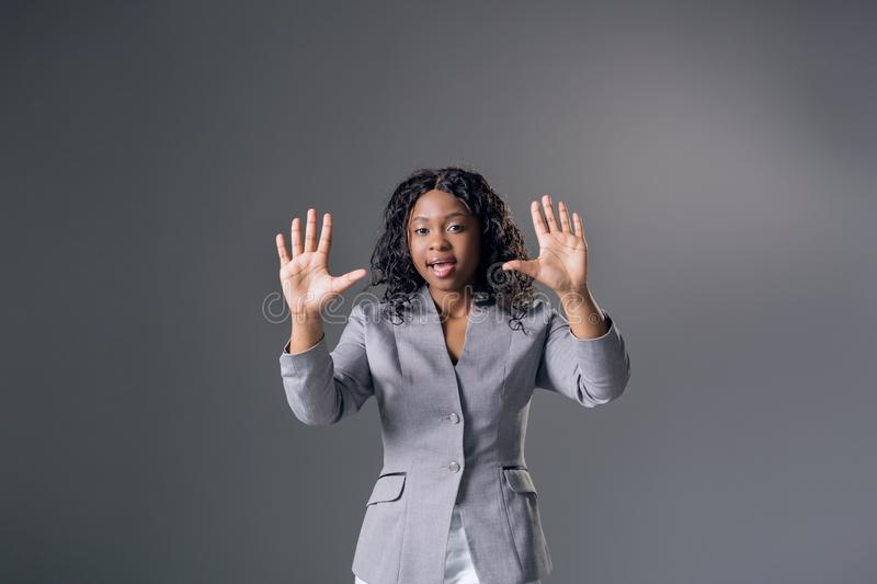 Portrait dark-skinned beautiful woman a gray jacket with dark curly hair, looking into the camera and screams stock photography
