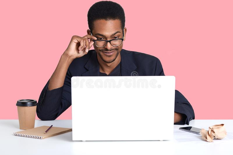 Portrait of dark skinned man works with laptop. Handsome black male sits at desk wears suit, touches his spectacles with hand, royalty free stock photos