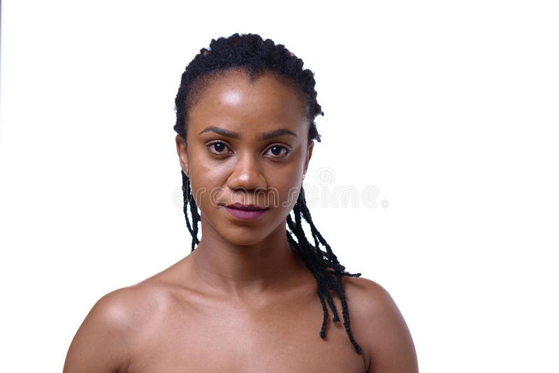 Portrait of dark-skinned woman on white background. Portrait of dark-skinned woman with bare shoulders against white background stock photography