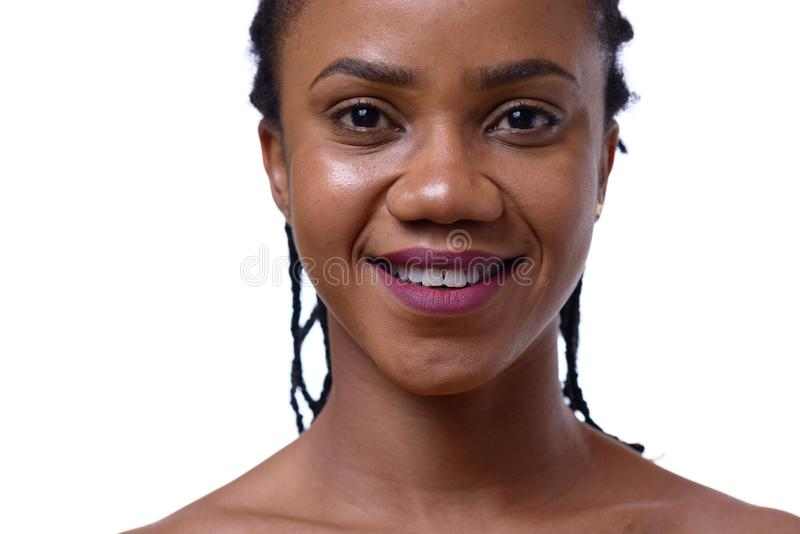 Portrait of dark-skinned woman on white background. Portrait of dark-skinned woman with bare shoulders against white background, close up view stock photo