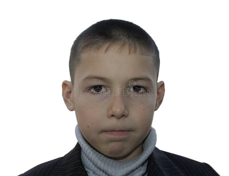 Portrait de 8 années de garçon avec le visage sérieux et les lèvres étroitement serrées d'isolement sur le blanc image stock