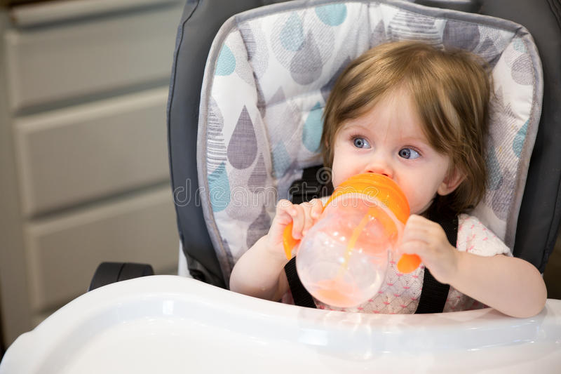 Portrait de bébé buvant de la bouteille se reposant dans le highchair images stock