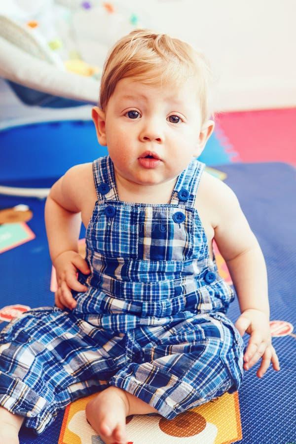 Portrait de bébé garçon de sourire caucasien blond adorable mignon avec les yeux bruns dans la barboteuse bleue se reposant sur l images libres de droits