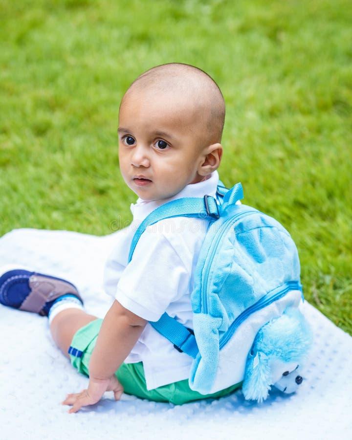 Portrait de bébé garçon indien avec le sac à dos se reposant sur la terre image stock