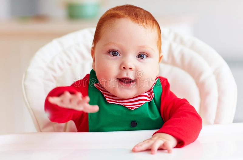 Portrait de bébé garçon infantile mignon dans le costume d'elfe se reposant dans le highchair images stock