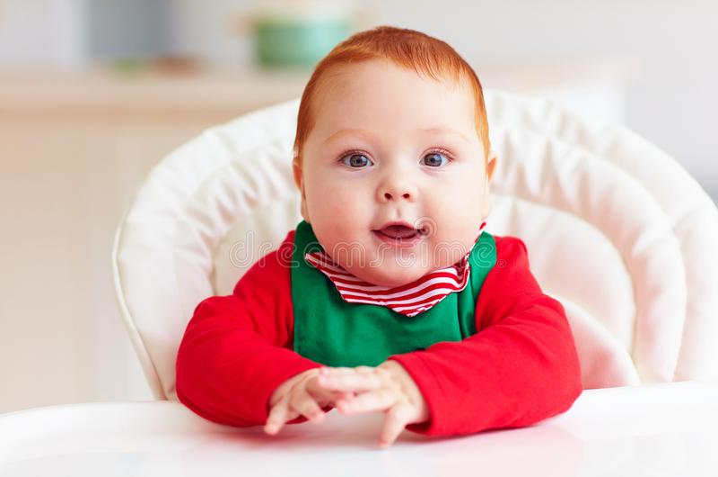 Portrait de bébé garçon infantile mignon dans le costume d'elfe se reposant dans le highchair photo stock