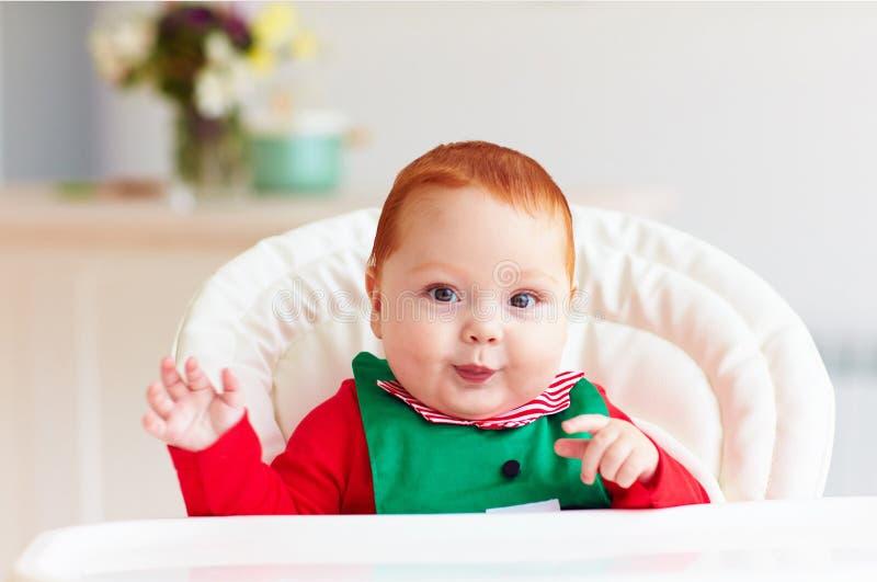Portrait de bébé garçon infantile mignon dans le costume d'elfe se reposant dans le highchair image stock