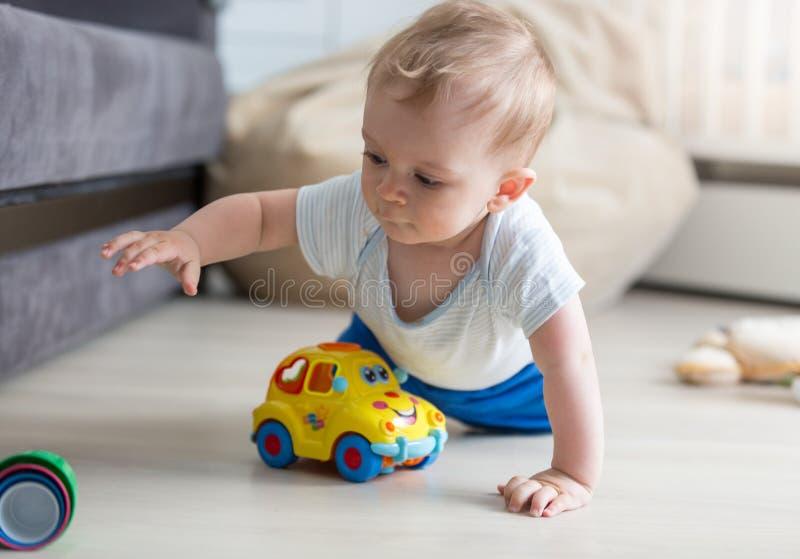 Portrait de bébé garçon mignon rampant sur le plancher et jouant avec le jouet photos stock