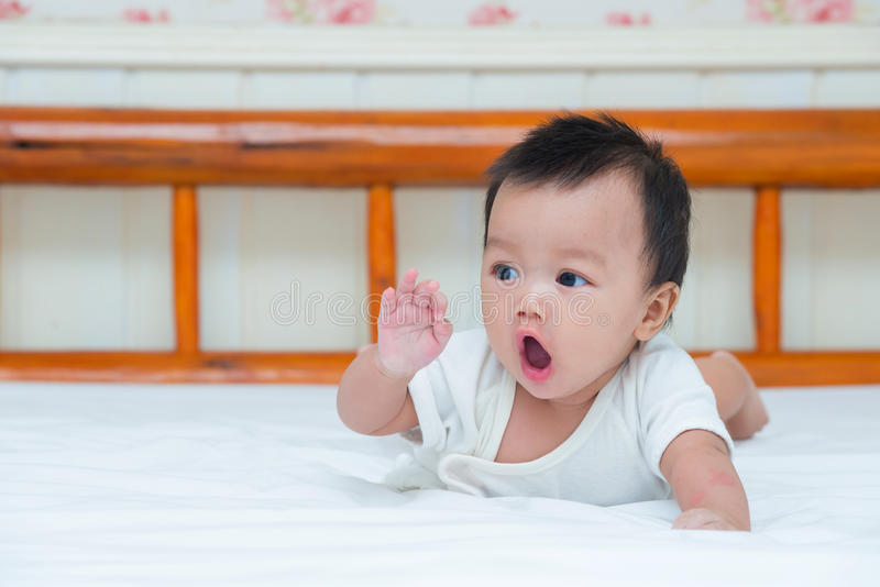 Portrait de bébé mignon sur le lit photographie stock