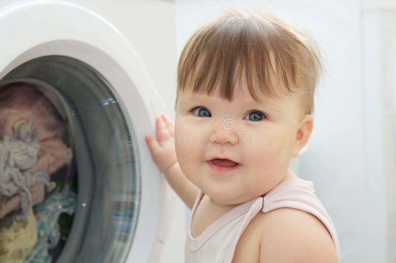 Portrait de bébé près de machine à laver, ayant l'amusement et jouant avec le joint images stock