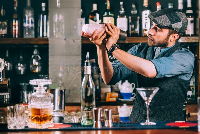 Portrait de barman préparant des cocktails, utilisant le dispositif trembleur et versant des boissons image stock