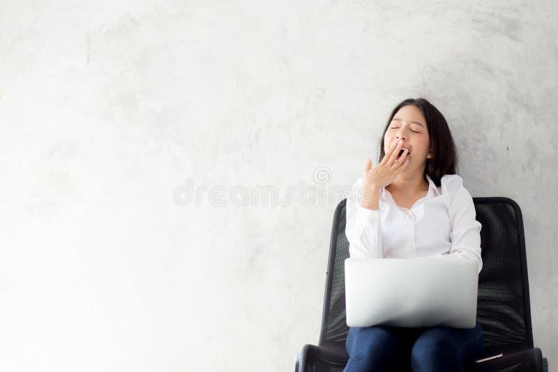 Portrait de beau bâillement asiatique de jeune femme à son lieu de travail avec l'ordinateur portable sur le fond de ciment photo stock