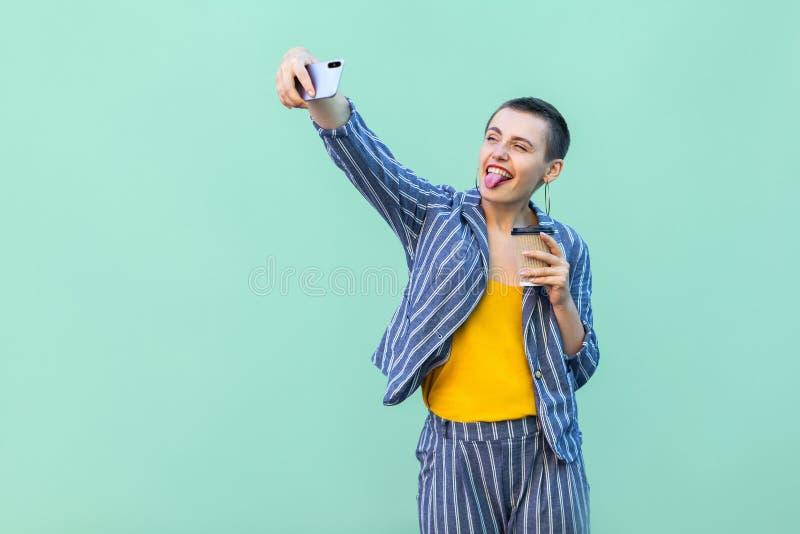Portrait de beau blogger puéril avec la jeune femme de cheveux courts dans la position rayée de costume, faisant le selfie et mon image libre de droits