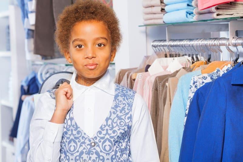 Portrait de beau garçon africain près des vêtements photographie stock
