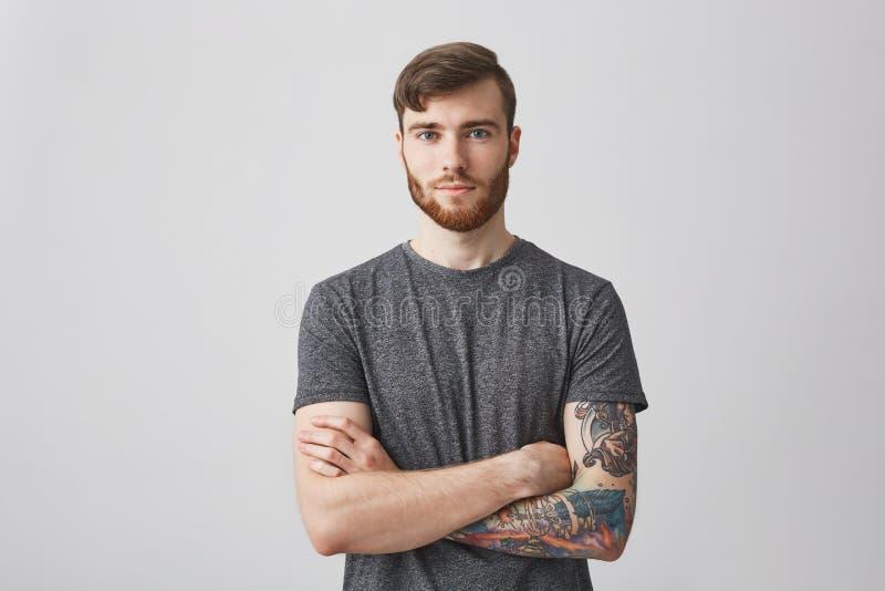Portrait de beau jeune homme avec la barbe de gingembre et la main tatouée regardant in camera avec le sourire et le calme doux photographie stock